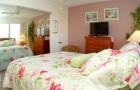 Bedroom with TV, mirrored closet doors and queen size bed